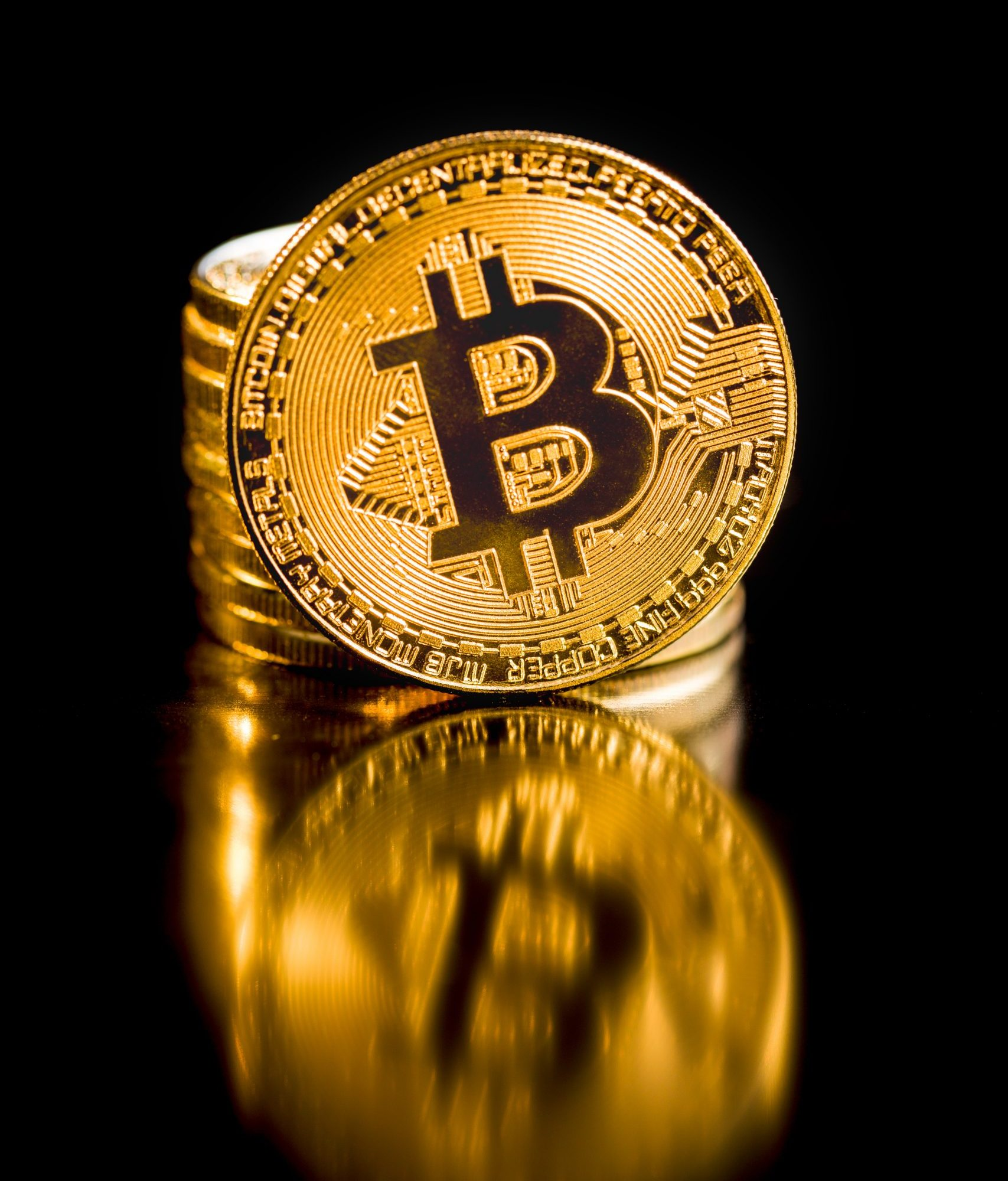 Golden bitcoins. Cryptocurrency on black background.